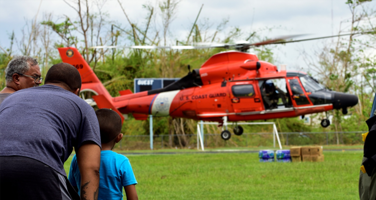 A Coast Guard Air Station Borinquen, Puerto Rico, MH-65 Dolphin helicopter crew takes off from a soccer field in Aguada, Puerto Rico, Oct. 11, 2017.