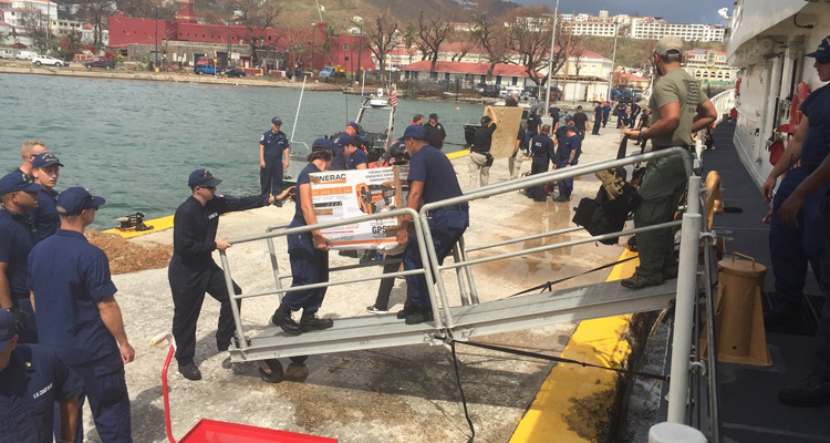 Coast Guard Cutter Joseph Tezanos crewmembers offload supplies, equipment and emergency personnel