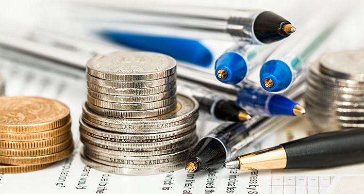 Close-up of two stacks of coins and several pens, posed meticulously.