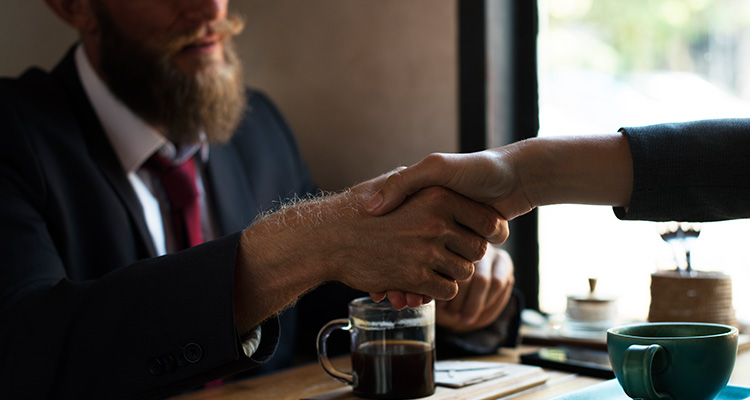 Close-up shot of two people shaking hands over a table of paperwork and coffee.