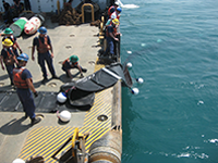 personnel deploy an underwater barrier